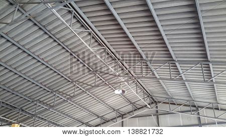 view from beneath of sloping ceiling with steel girders, hanging metal light, cafeteria roof at Buddhist temple, Ranot, Thailand