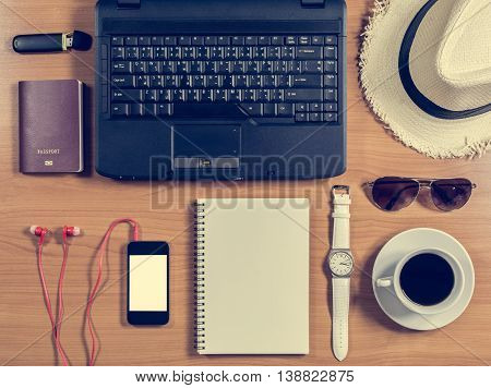 Office Desk With Computer, Supplies, Coffee Cup, Passport, Hat, Sunglasses And Wristwatch.