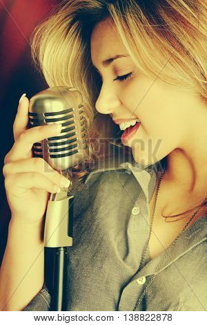 Beautiful woman singing into microphone