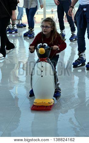 Sydney, Australia - Jul 17, 2016. A little girl ice skating with a Penguin Skate Aid on Bondi ice rink. Australia's only beachside ice rink is on Bondi beach.