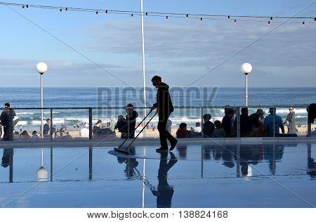 Sydney Australia - Jul 17 2016. Man cleaning the ice on Bondi ice rink. Australia's only beachside ice rink is on Bondi beach.
