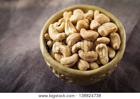 Roasted cashews.  Organic roasted cashews in a bowl on burlap background. Natural morning light, toned image, selective focus