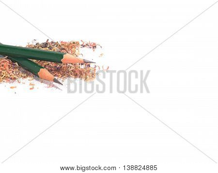 two sharpened green pencils stack on a pile of pencil sawdust isolated on white background