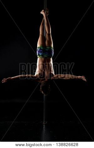 Pole dance. Image of strong man hanging upside down