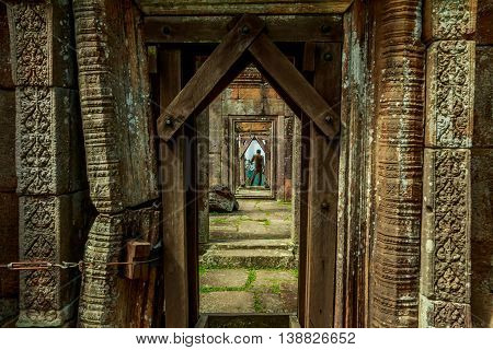 A soldier stands in the doorway of ancient Khmer ruins in Cambodia