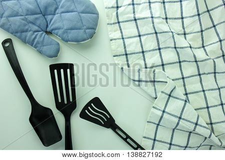 black ladle kitchen glove and spade of frying pan on the white table