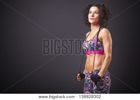Fitness woman posing with a jumping rope on black background