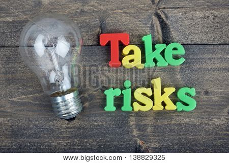 Take risks word on wooden table