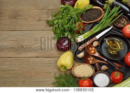 Various vegetables and pan on a wooden background