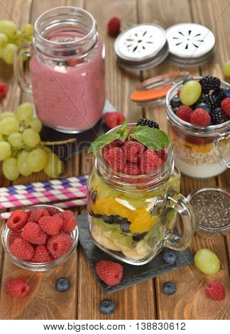 Fruit salad in a jar on a wooden background