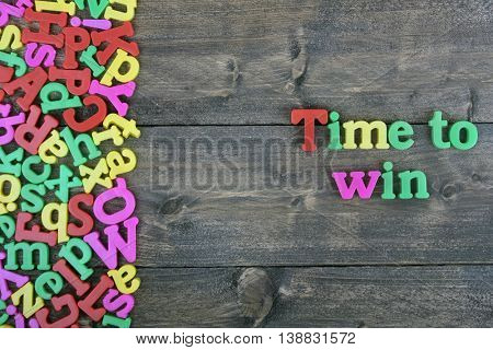 Time to win word on wooden table