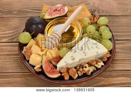 Blue cheese with grapes figs and honey on wooden background