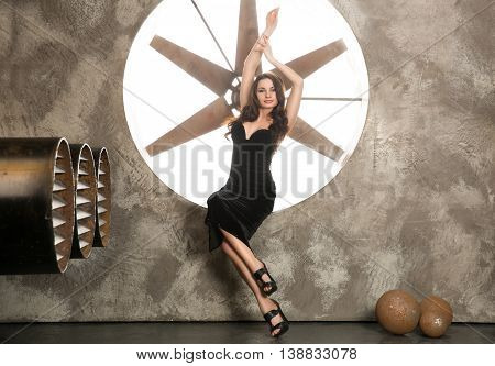 Elegant and beautiful top model near ventilation pipes posing with huge turbo ventilator behind her were lights coming through.