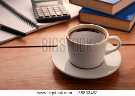 Break Time Concept. Cup of coffee with notebook, calculator and pen on wooden table