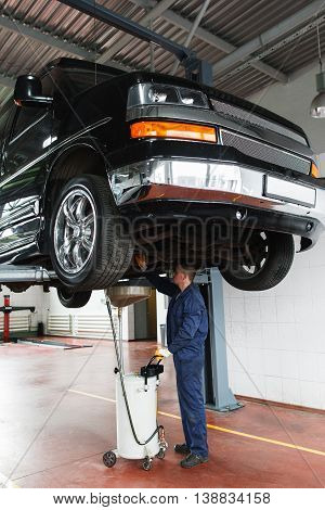 Oil change in SUV, service maintenance. Car raised up on lift in garage, mechanic works under it with special equipment