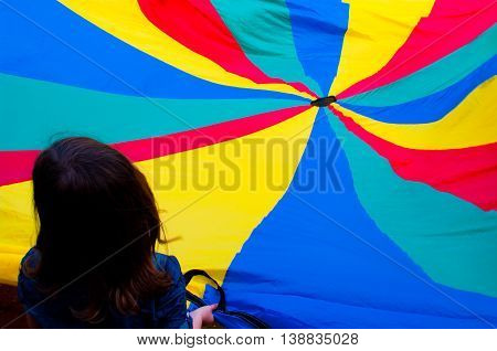 Children spread a colored cloth for fun
