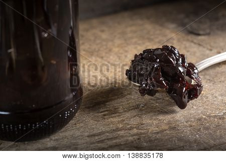 Cherry jam in spoon and one preserving glass jar over old wooden rustic background