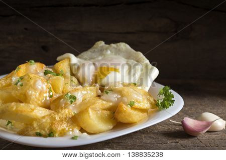 Homemade french fries (potatoes) with garlic sauce and egg on wooden rustic background