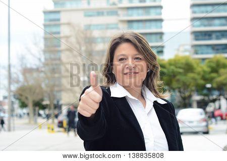 Portrait of beautiful business woman doing ok gesture. Success concept. Outdoors.