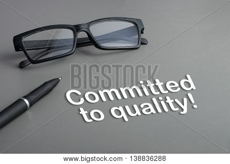 Concept : Committed to quality !. business concept. pen and glasses