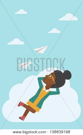 An african-american business woman lying on a cloud and looking at flying paper plane. Business woman relaxing on a cloud. Vector flat design illustration. Vertical layout.