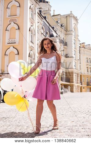 Girl with colorful latex balloons urban scene outdoors