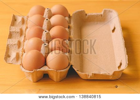 Ten eggs in cardboard box retro toned selective focus