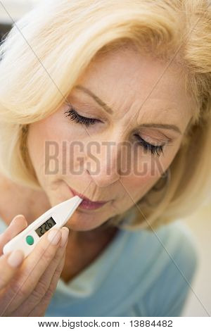 Woman Taking Her Temperature With Thermometer