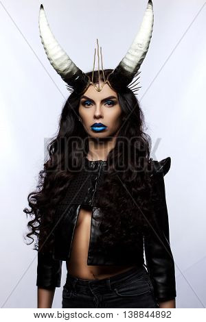 Young Girl With Horns On His Head On A White Background. Woman With Long Black Hair.