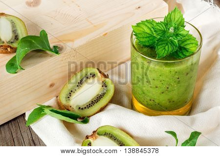 Glass fruit and vegetable smoothies out of kiwi arugula closeup