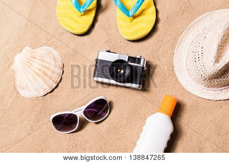 Summer vacation composition with camera, pair of yellow flip flop sandals, hat, sunglasses, sun cream and other stuff on a beach. Sand background, studio shot, flat lay.