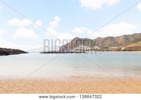 view of Santa Cruz beach Las Teresitas with palms at sunny summer day, Tenerife island, Canaries Spain