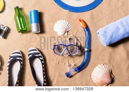Summer vacation composition with goggles, shoes, shell, towel, bottle, can and other stuff on a beach. Sand background, studio shot, flat lay.