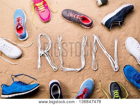 Various colorful running shoes and run sign made of shoelaces against sand background, studio shot, flat lay