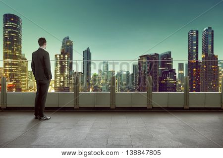 Businessman Standing On A Roof And Looking At City On Night Time