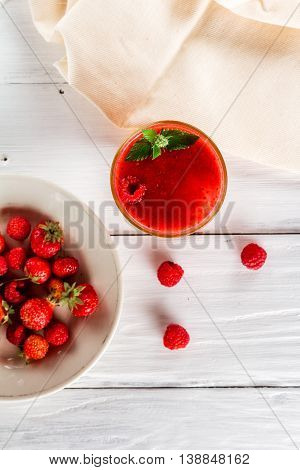 Glass of berry smoothie plate with raspberries and strawberries. Top view