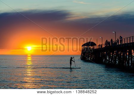 Standup paddleboarding silhouette of a man at Henely Beach near the jetty South Australia