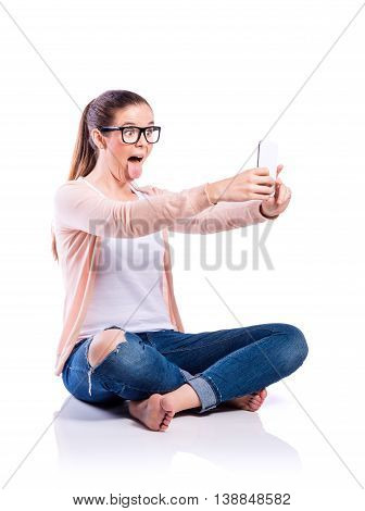 Teenage girl in white t-shirt, pink cardigan, jeans and trendy black eyeglasses, holding a smart phone, sticking tongue out, taking selfie, sitting on the floor, young beautiful woman, studio shot on white background, isolated