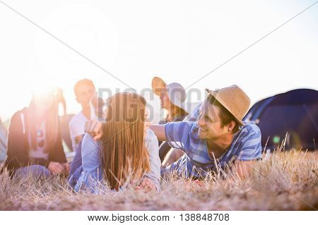 Group of teenage boys and girls at summer music festival, young couple, lying on the ground in front of tents