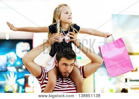 Happy family in shopping mall. Daughter is enjoying on father's shoulders.