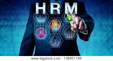 Human resources manager is pressing HRM on an interactive touch screen monitor. Business metaphor and acronym for Human Resource Management. Concept for work force planning.