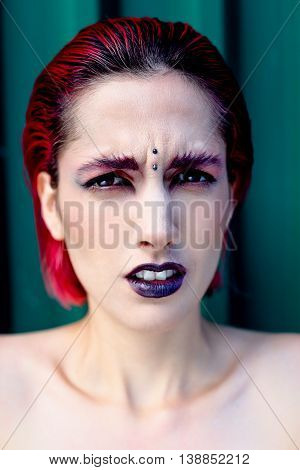 Attractive young woman with colorful makeup, red hairstyle, expressive eyes and piercing on forehead, green metal wall on background