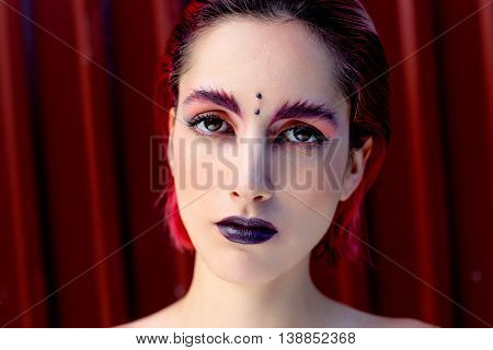Attractive young woman with colorful makeup, red hairstyle, expressive eyes and piercing on forehead, red metal wall on background