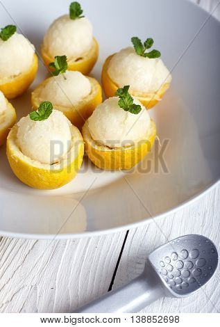 Lemon icecream served in half of lemon in white plate on white background. Ice creame scoop near it.
