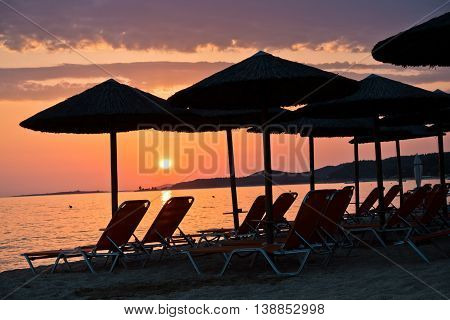 Sandy beach with stray sunshades and orange chairs at sunset in Sithonia, Greece