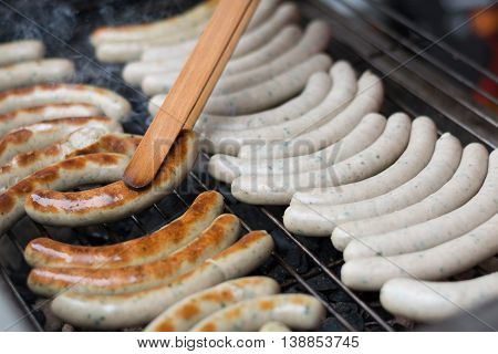 Sausages are turned on charcoal grill with tongs