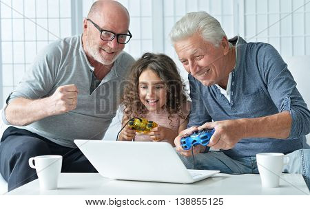 senior men and granddaughter having fun and playing on laptop  at home