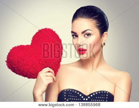 Sexy model Woman portrait. Gorgeous young brunette woman holding heart shaped red pillow. Perfect make up. In love