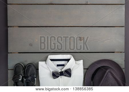 Men's Outfit On Wooden Background. Kids Fashion Clothes. Grey Fedora, White Shirt, Black Bow Tie And