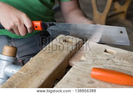 Carpenter working at workbench with Japanese saw